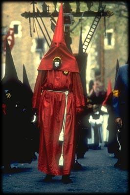 la procession de la sanch,En tête du cortège de la Croix des Outrances entourée des tambours crêpés de noir et devant le « caparutxa » rouge qui rythme la marche lente de la procession au son de la cloche de fer.
